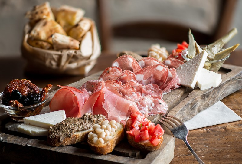 Tuscan specialties, a plate of different hams, pecorino cheeses, black olives, tuscan canapés, fresh tomato bruschetta and delicious artichokes, served at Boccanegra Florence Osteria and Restaurant
