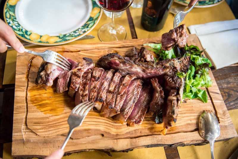 Amici a pranzo al Boccanegra condividono una tagliata di bistecca con radicchi servita sul tagliere